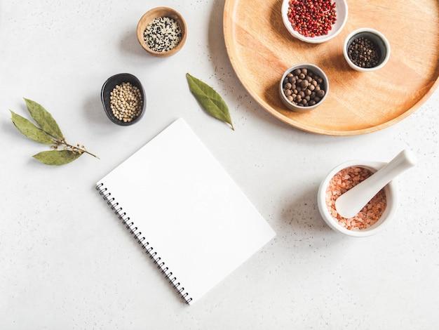 Bloco de notas de cozinha simulado para texto culinário e várias especiarias na tigela e sal marinho em argamassa branca