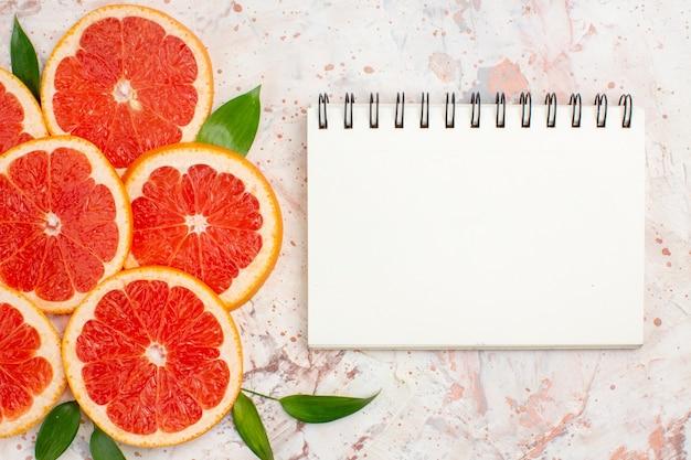 Bloco de notas de fatias de toranjas deliciosas de vista superior na mesa de nudismo