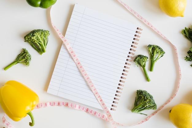 Bloco de notas de fita métrica com páginas limpas e vegetais frescos e frutas em fundo branco