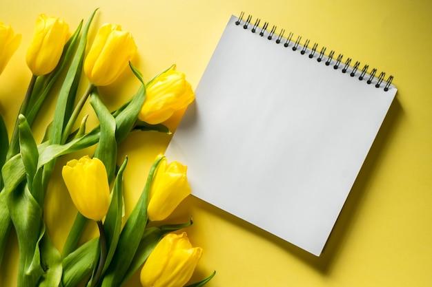 Bloco de notas de maquete com buquê de tulipas em vista superior em foto panorâmica de fundo colorido amarelo