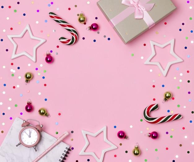 Bloco de notas de mármore com caneta, presente e ornamentos em fundo rosa