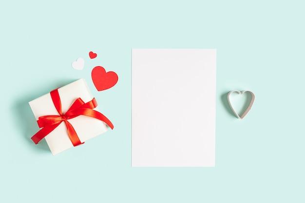 Bloco de notas de mesa de papel em branco. camada plana de fundo azul de mesa de trabalho com presente de dia dos namorados