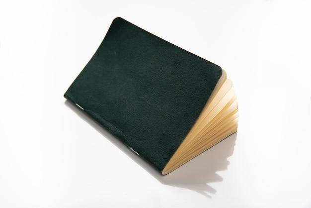Bloco de notas de papel com capa verde sobre fundo branco.