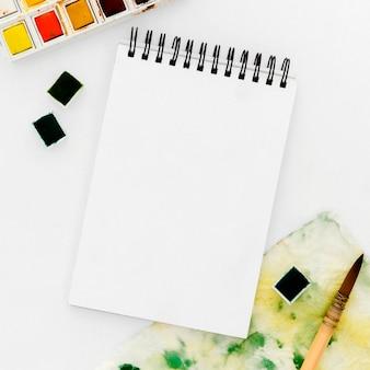 Bloco de notas de vista superior com aquarelas em cima da mesa