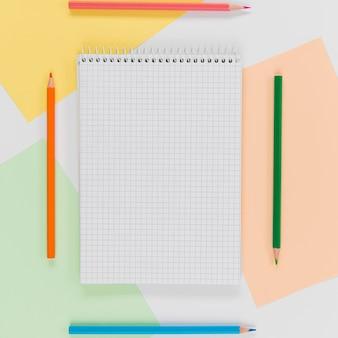 Bloco de notas de vista superior com lápis em cima da mesa