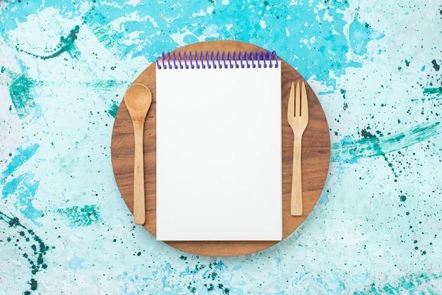 Bloco de notas de vista superior e talheres de madeira no fundo azul claro, caneta, papel, foto colorida de madeira