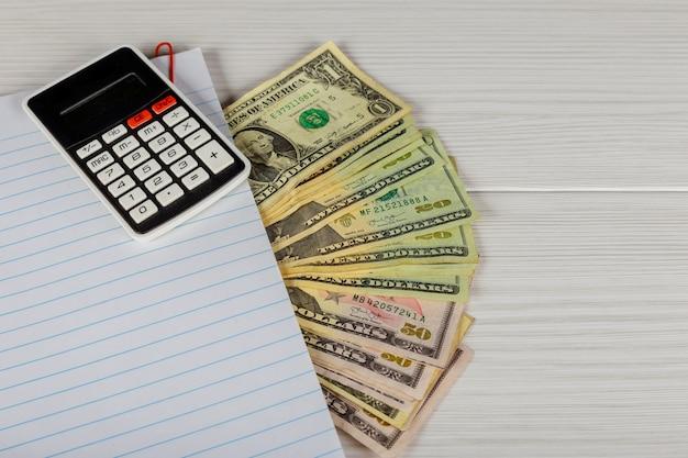 Bloco de notas, dinheiro e calculadora na mesa de madeira.