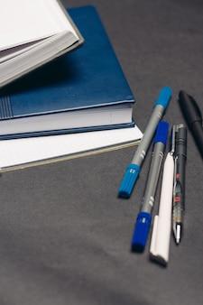 Bloco de notas, documentos, livros, canetas, área de trabalho, cinza, fundo, escritório. foto de alta qualidade