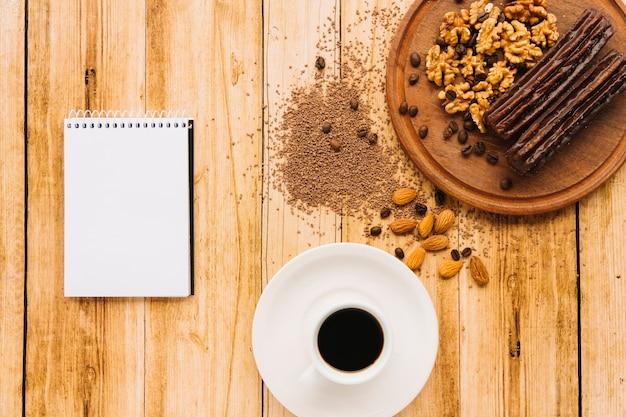 Bloco de notas e café perto de nozes na placa de corte