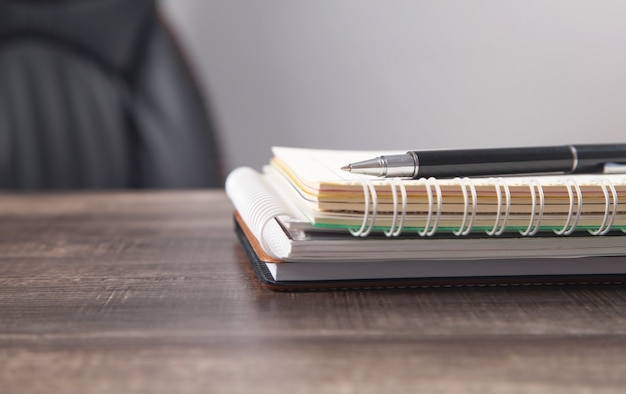 Bloco de notas e caneta na mesa de negócios.
