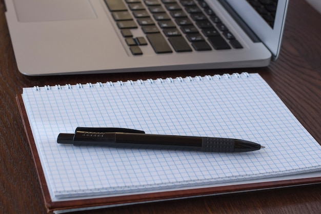 Bloco de notas e caneta perto do laptop na mesa
