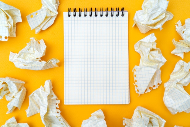 Bloco de notas e folhas de papel amarrotadas em um fundo amarelo.