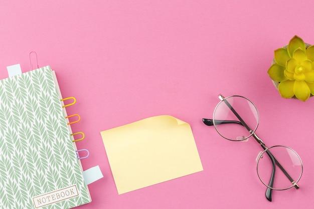 Bloco de notas e folhas para anotações em fundo rosa