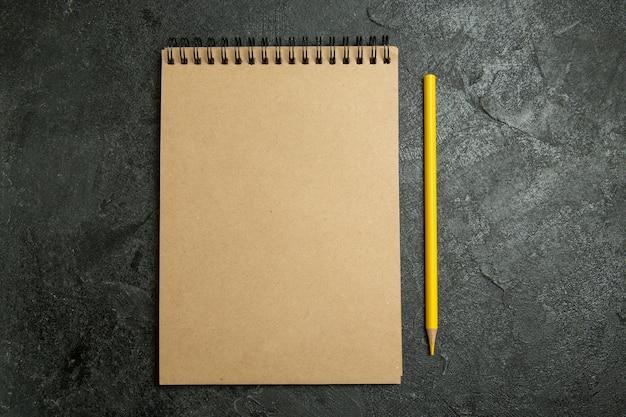 Bloco de notas e lápis de vista superior no espaço cinza