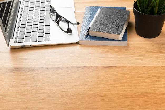 Bloco de notas e laptop na mesa de madeira