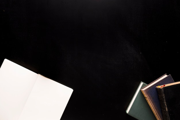 Bloco de notas e livros na mesa preta