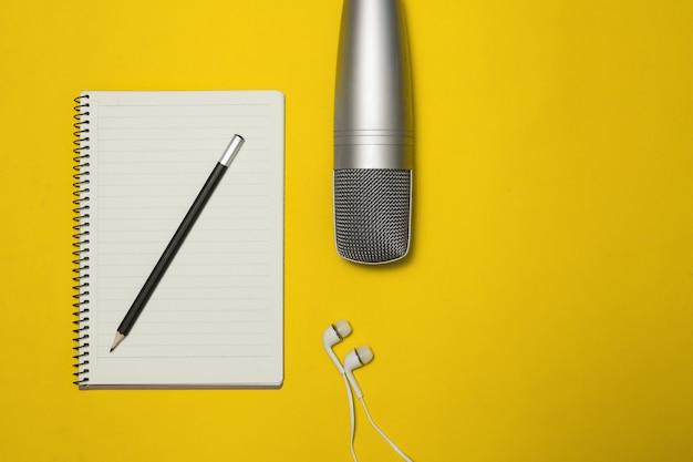 Bloco de notas e microfone no fundo da cor