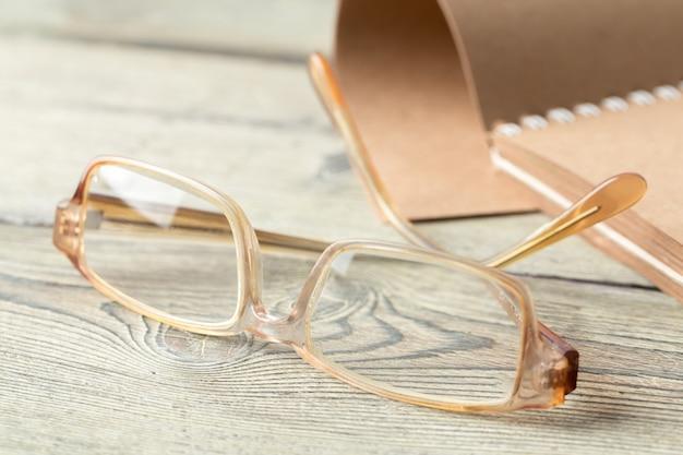Bloco de notas e óculos em cima da mesa