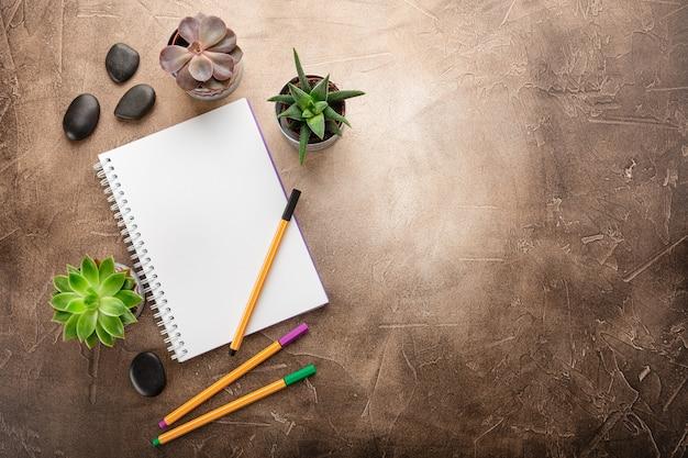 Bloco de notas e suculentas na mesa vista superior