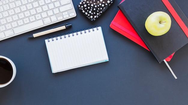 Bloco de notas e teclado perto da xícara de café e maçã