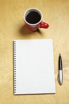 Bloco de notas e xícara de café em uma mesa de madeira