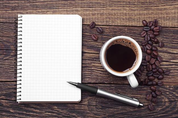 Bloco de notas e xícara de café na mesa de madeira, vista superior