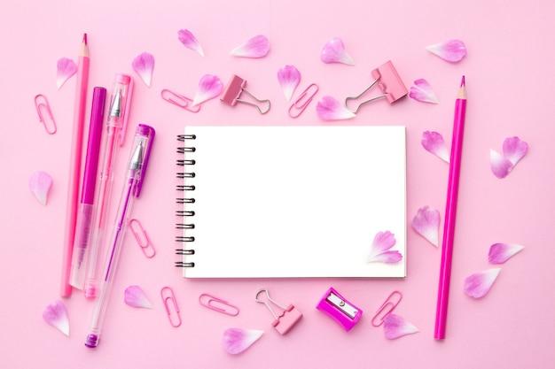 Bloco de notas em branco branco, canetas e lápis cor de rosa, papelaria e pétalas de flores cor de rosa em verso plano