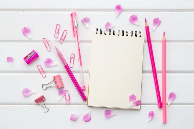 Bloco de notas em branco branco, canetas e lápis rosa, papelaria e pétalas de flores rosa em madeira branca, camada plana