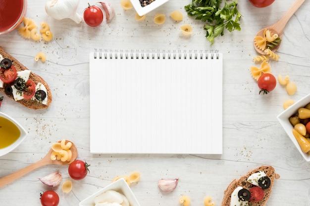 Bloco de notas em branco cercado com macarrão cru e ingredientes de comida italiana sobre a mesa branca