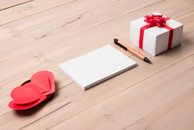 Bloco de notas em branco com caixa de presente na mesa