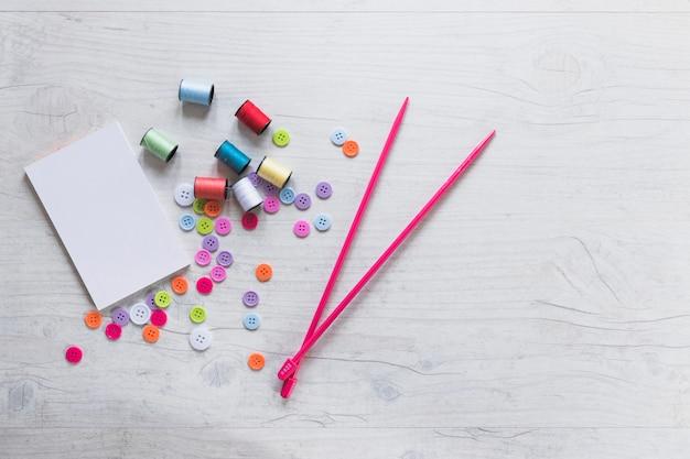 Bloco de notas em branco com carretéis; botões e agulhas de malha no plano de fundo texturizado