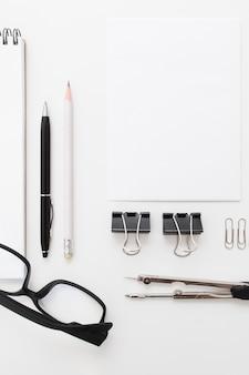 Bloco de notas em branco com clipes, canetas e óculos