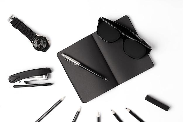 Bloco de notas em branco com clipes, canetas e vidros planos. vista superior de um conjunto de materiais de escritório pretos e óculos em um fundo branco
