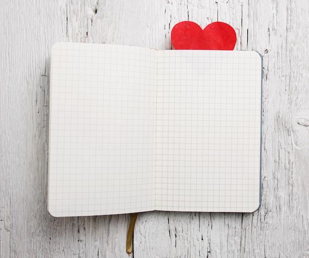 Bloco de notas em branco com coração vermelho na superfície de madeira