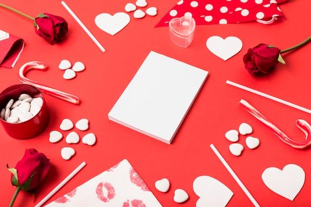 Bloco de notas em branco com corações na mesa