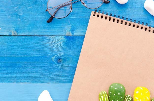 Bloco de notas em branco com óculos e cactos