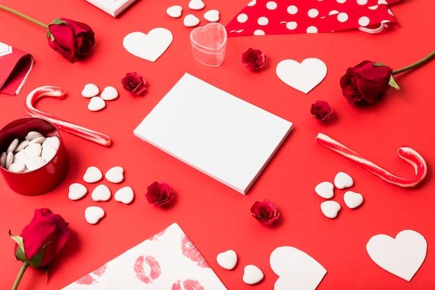 Bloco de notas em branco com pequenos corações na mesa