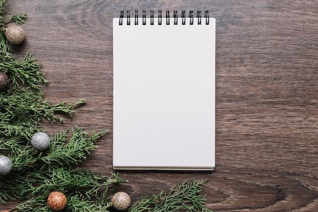 Bloco de notas em branco com ramos verdes na mesa