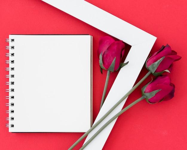 Bloco de notas em branco com rosas vermelhas no quadro de luz