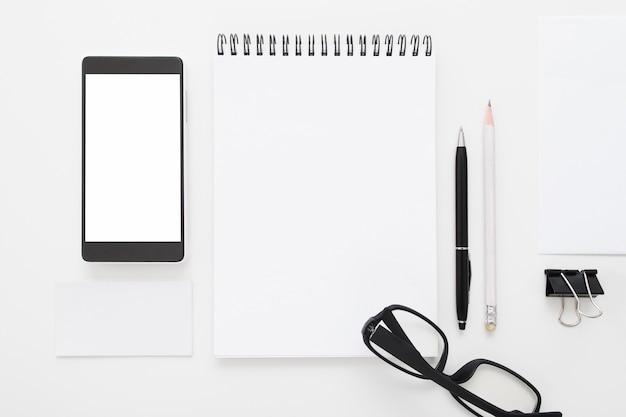 Bloco de notas em branco com smartphone e óculos