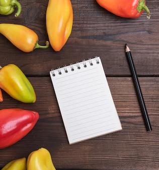 Bloco de notas em branco com um lápis de madeira preto na mesa marrom