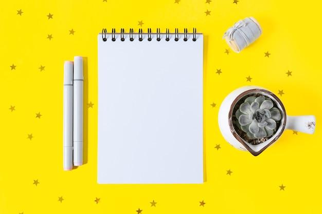 Bloco de notas em branco da área de trabalho com espaço para texto. camada plana do fundo amarelo da mesa de trabalho