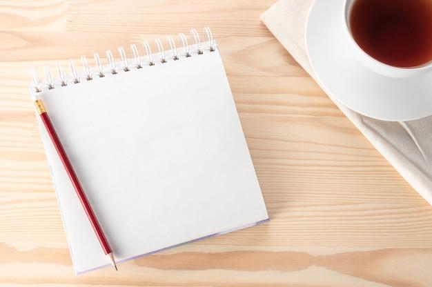 Bloco de notas em branco de maquete com caneta, caderno e xícara de chá na mesa de madeira.