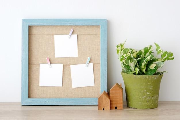 Bloco de notas em branco de papel branco pendurado no fundo do frame de madeira azul vintage