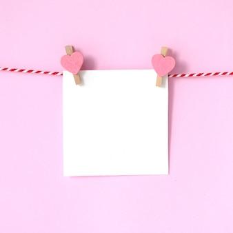 Bloco de notas em branco de papel branco pendurado no fundo rosa