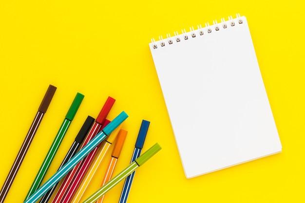 Bloco de notas em branco e canetas hidrográficas coloridas sobre fundo amarelo. marcadores multicoloridos para desenho infantil.