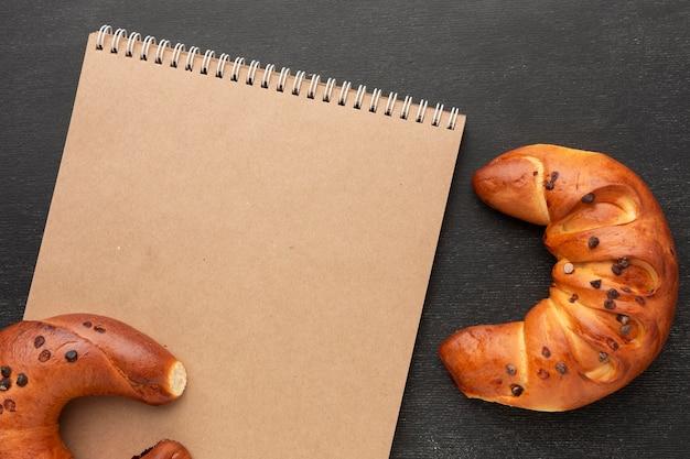Bloco de notas em branco e croissants
