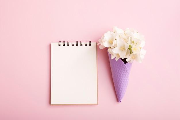 Bloco de notas em branco e flores em um cone de waffle em um fundo rosa. em branco para parabéns, notas