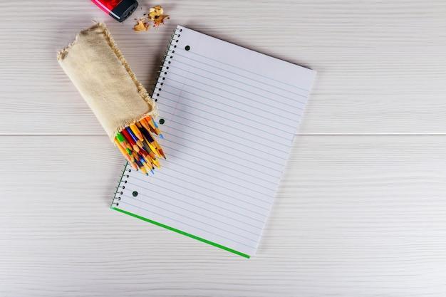 Bloco de notas em branco e lápis de cor na madeira