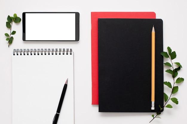 Bloco de notas em branco e tela do smartphone com suprimentos